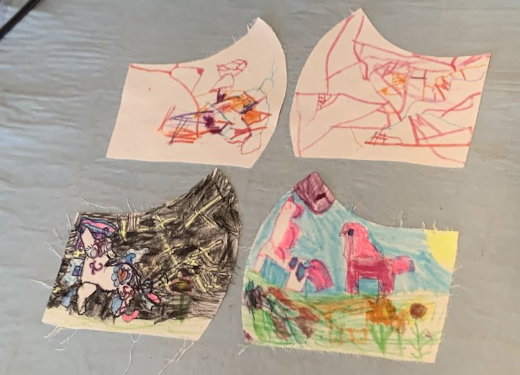 Image shows four, previously white, pattern pieces that had been colored by the girls. Zoey's two pieces are at the top and are more scribble doodled on while Ada drew a more detailed image to all the edges including unicorns, flowers, and the sun.