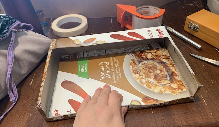 Image shows the box with the interior showing a reversed image of the missing piece of the box. Around it sits a mask on the grey bag of masks, masking tape, packing tape, X-Acto knife, X-Acto box, and scissors.