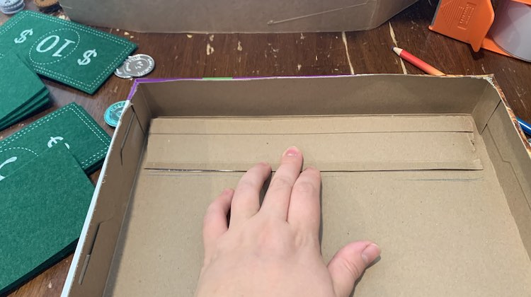 The strip from before is flipped over so it's along the top of the box and you can see the pencil marks below it and the tape showing through underneath it. My fingers are holding it down.
