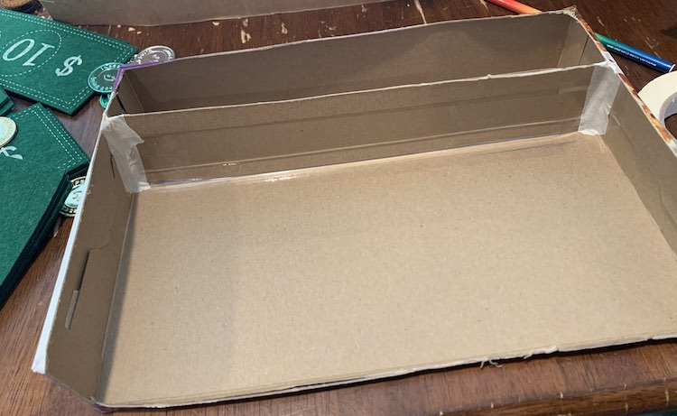 Image show a view above and to the front of the cereal box; when looking straight at it. The edges of the divider are taped down with beige tape.