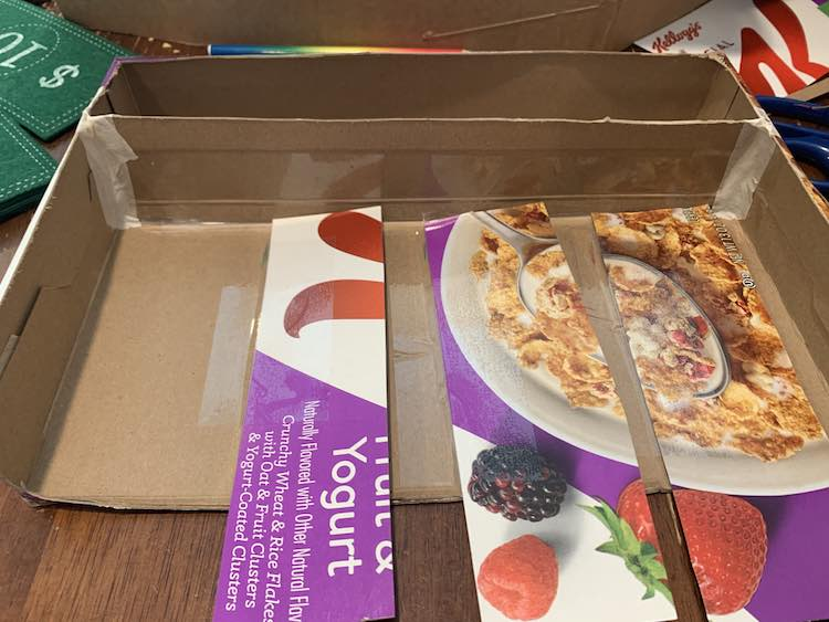 Image shows the same as before except this time the strips of cereal cardboard have been flipped over so the printed side is up and they're towards the right side now.