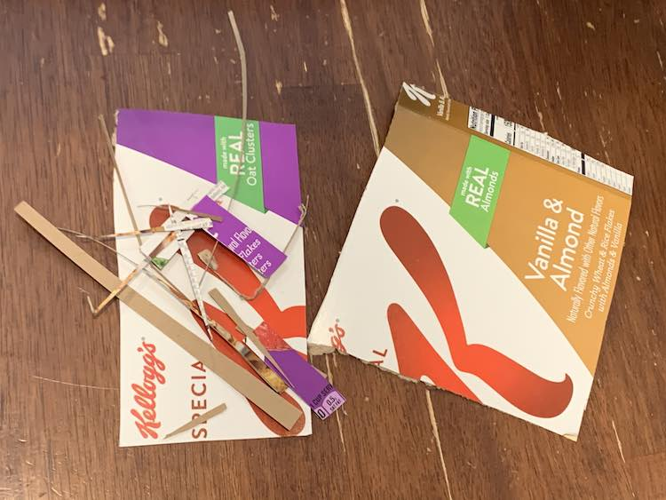 Image shows two larger pieces of cardboard and a lot of little sections, from trimming things to size, laid out on the table.