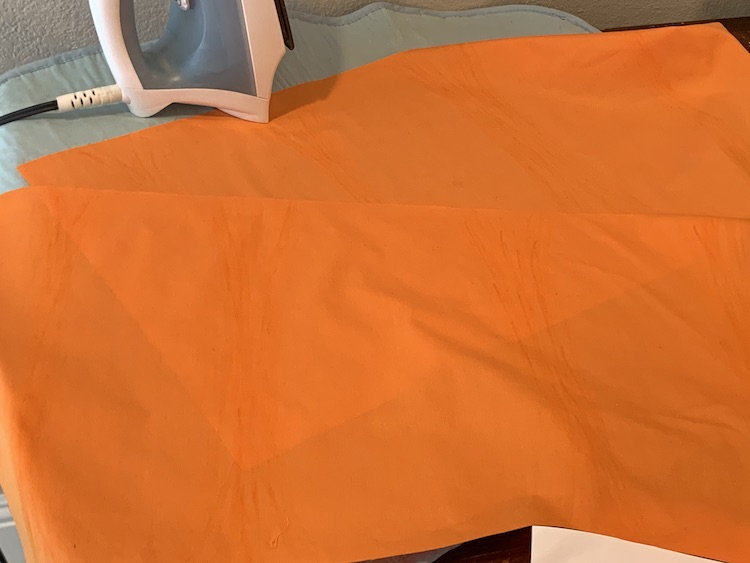 The two rectangles of orange fabric laid out on the ironing mat.