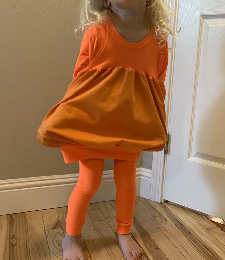 Front view of the pumpkin top with the sides spread out with Zoey's hands hidden in the pockets. The leggings are worn underneath the top.