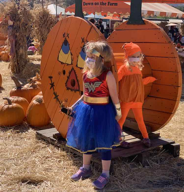 Both girls standing in front of another wooden pumpkin-like display with pumpkins laid out behind it. Ada stands in front looking off to the side while Zoey stands behind looking in the other direction.