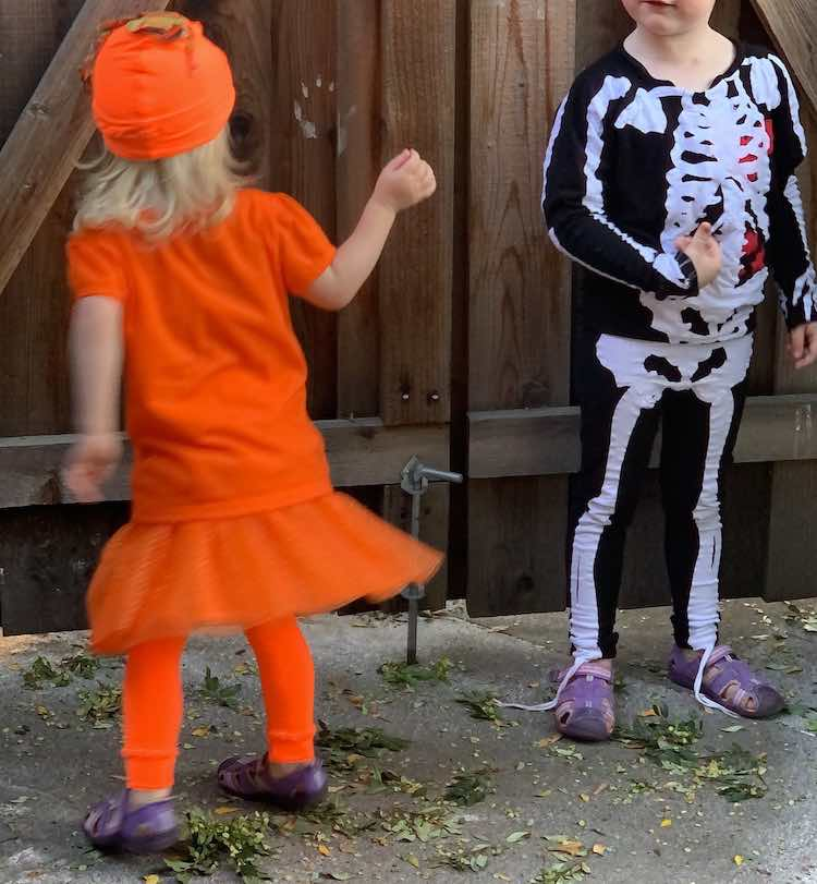 Image shows the back of Zoey's pumpkin costume as she twirls. To the right is Ada's swaying skeleton.