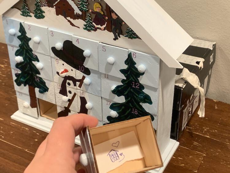 Image shows a closeup of the inside of a drawer showing the advent calendar with an arrow to the back and a heart. Behind it sits the rest of the advent calendar with a tape covered shoe box behind it.