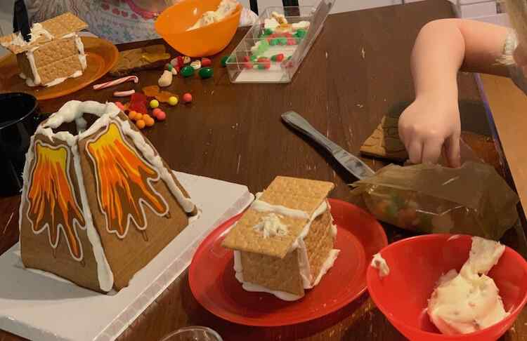 Image shows a table with a gingerbread volcano spouting colorful sugar paper lava. Behind and to the side of it the kids are seated with a graham cookie and icing house and candy to decorate it with.