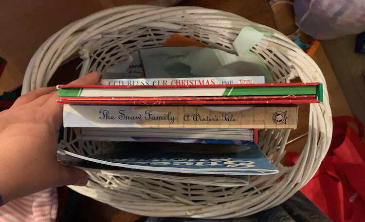 Image take from above looking down at a white wicker basket filled with Christmas themed books sitting upright inside it.