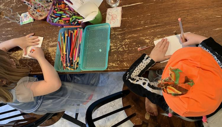 Image shows the kids sitting beside each other at the kitchen table. Between them sits a container of crayons, a container of pencil crayons, a marker holder, and a cup of blank stickers.