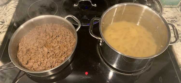 Image shows my stove with the front two larger burners being used and two glass lids behind them. The left saute pan has browned ground beef in it while the rightmost pot has just added penne pasta so the water hasn't yet come back up to a boil.