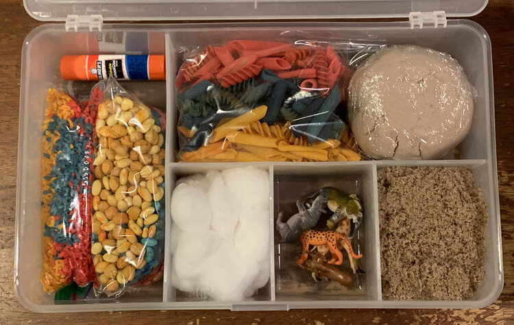 Image shows a sensory kit filled up with materials, glue stick, and toys. The lid is open to better see the contents. The items are listed in the caption below the image.