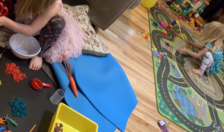 Photo shows the living room with Ada to the left making some food dish with her pasta dinosaurs. Zoey sits to the right with her dinosaurs waiting to go on the slide.
