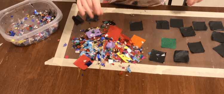 Image shows the same contact paper and container with supplies as the previous image. The difference is the pile of confetti and tissue squares dumped in the corner closest to the camera.