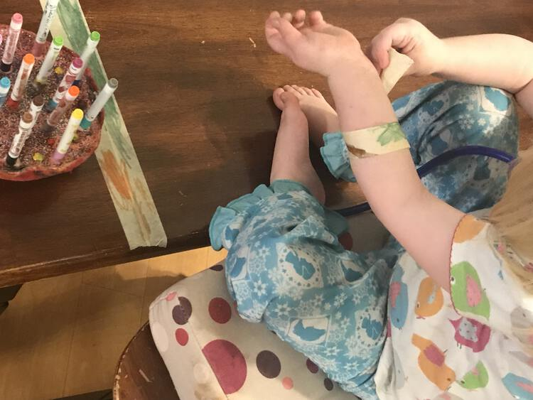 Image shows Ada sitting on her chair in front of the bench wrapping a decorated masking tape bandage around her arm. In the background are the other stripes of tape and the felt pens.