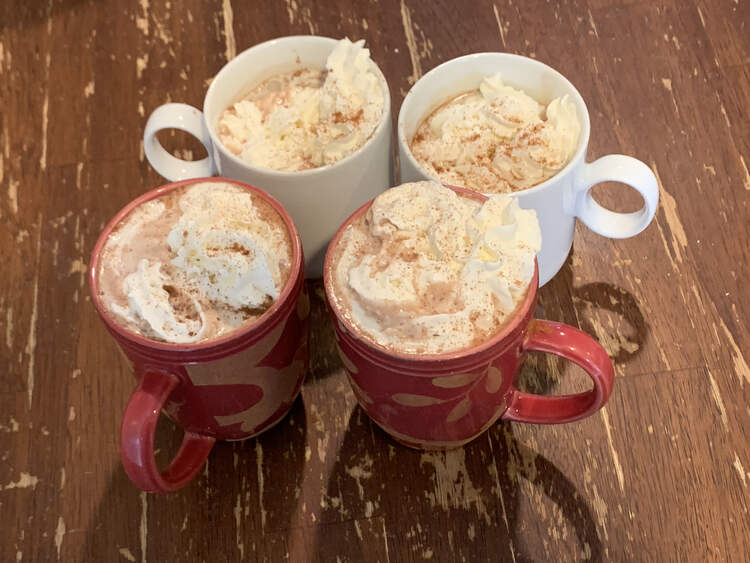 Image shows four cups (two red and two white) sitting on a table. All are filled with hot chocolate, topped with whip cream, and sprinkled with extra toppings.