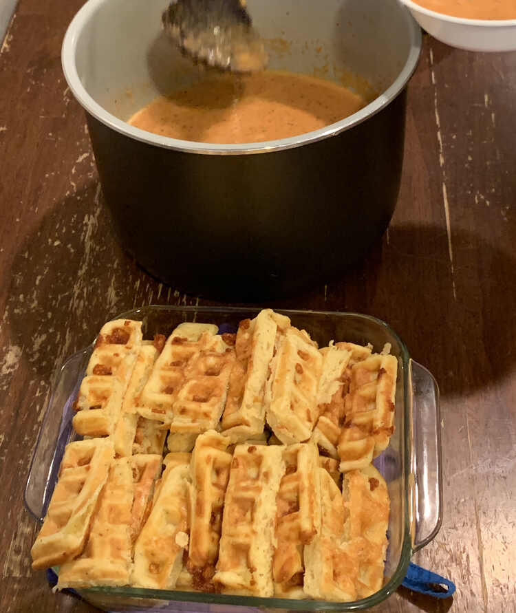 Image shows a pot of tomato soup (in a Ninja Foodi liner) behind a square casserole dish holding the sliced waffle dippers.