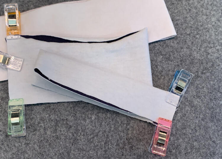 Image shows the properly folded cuff with a pink and blue clip holding it tightly together. In the background are two bands that haven't been folded enough yet.