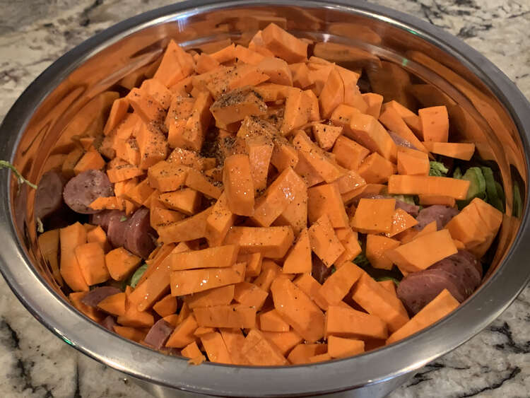 Image shows a bowl of yams with green Brussel sprouts and brown sausages poking through. There is oil and black flecks of pepper in the center back.