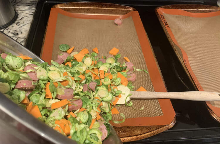 Image shows two cookie sheets lined with an orange bordered Silpat® liner. The metal bowl is angled over the left one as the veggie mix is poured out. A spatula is laid on the cookie sheet waiting to be used to get the last out.