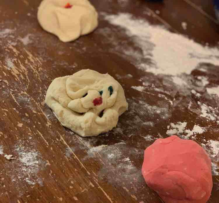 Image shows three different balls of playdough in different states on a flour, white powder, coated table. The front one is fully one shade of pink, the center one is still white but slightly misshapen with drops of blue and red on it (for purple), the back ball is more nest shape and blurred with yellow dye in the center.