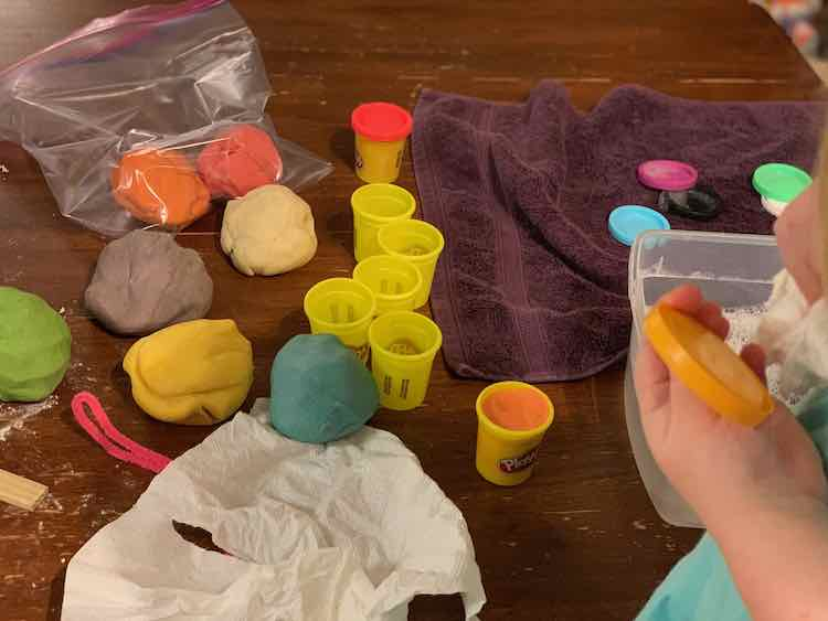 Image shows Ada washing a yellow Play-Doh lid with a white washcloth as a bin of soapy water and some soapy lids on a purple towel sit behind her. Beside that is a lidded red Play-Doh container, several empty and dried containers, and one container filled with orange playdough. Beside this sits several large balls of playdough and behind that a freezer bag with a smaller ball of pink and orange lay the remnants of the containers.