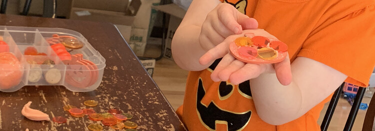 Image shows Zoey holding a glittery wooden pumpkin with plastic bingo disc 'glued' on with playdough.