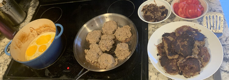 Image shows my cooking layout while frying the hash cakes and eggs after slicing some tomatoes.