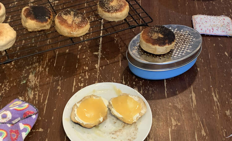 Image shows a sliced English muffin on a saucer topped with cream cheese and lemon curd. In the background sits a English muffin resting on a zester with a wire rack holding the rest.