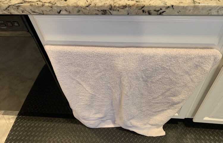 Image shows a white towel sticking out of the top of the under-sink cupboard and falling to the floor.