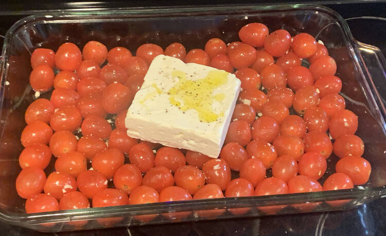 Image shows a glass casserole dish filled with a single layer of oiled cherry tomatoes with a white block of feta cheese in the center. The cheese has a yellow pool of oil and black pepper flecks. Amongst the tomatoes you can see the odd black fleck and minced garlic bits.