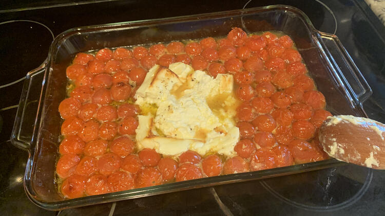 Image shows the glass casserole dish filled with deflated tomatoes in liquid and a slightly misshapen block of feta in the center. You can see the spoon section of the wooden utensil as it rests over the corner of the casserole dish.