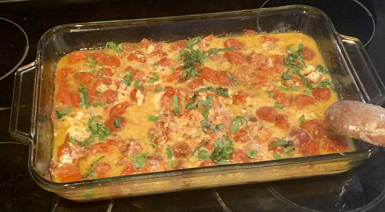 Image shows a yellow-ish liquid in a glass casserole dish filled with round red tomatoes, chunks of white feta, dark splotches of balsamic vinegar, and slivered green basil. The spoon, once again, is leaned up over the corner of the dish.