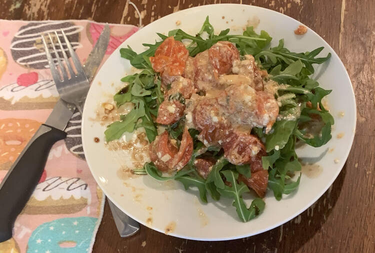Image shows a plate that appears to hold a salad as the single piece of toast is hidden underneath. It shows the tomato and feta mixture on top of a pile of arugula. Beside the plate sits a donut decorated napkin underneath a dirtied fork and steak knife.