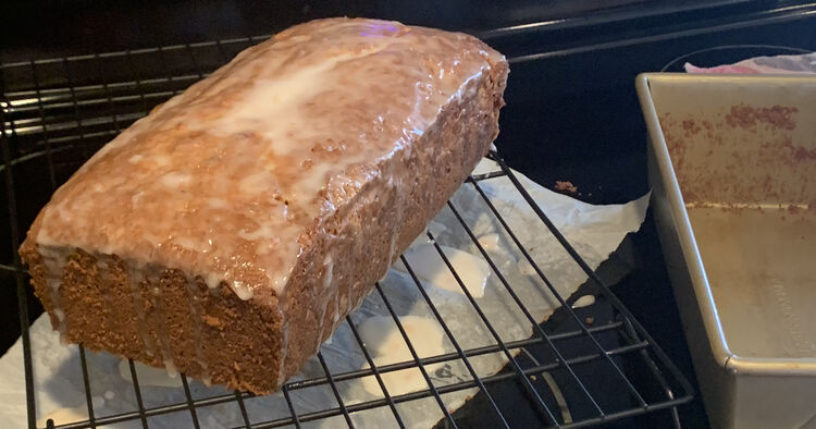 Image shows the loaf as one piece only with white dripping off it's ends on to the parchment below the cooling rack. Beside it sits a dirtied but emptied loaf pan.