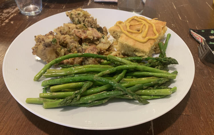 Image shows a white with mustard swirled cornbread, the potato dish, and a pile of bright green asparagus.