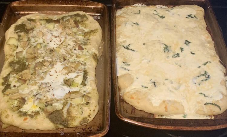 Same image as before with the two pizzas side by side but now they're all cheese melty or egg cooked fresh from the oven.