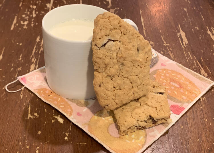 Image shows a white mug filled with milk on a cupcake decorated napkin on the kitchen table. Beside it sits one cookie, lying flat, and another leaned up vertically on the first cookie and leaning against the mug.