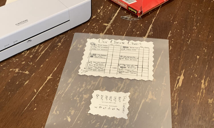 Image shows most of the laminator pouch with the larger chore chart closer to the top and the Tea Tracker turned on it's side closer to the bottom of the photo. In the background sits the thermal laminator and the package of laminating pouches.