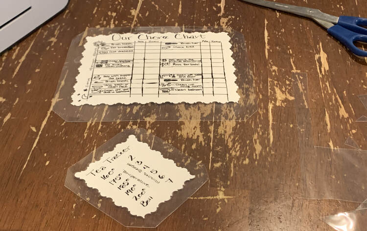 Image shows the laminated and trimmed Tea Tracker (in the front), Chore Chart (further to the back, scissors, laminator, and bits of scrap.