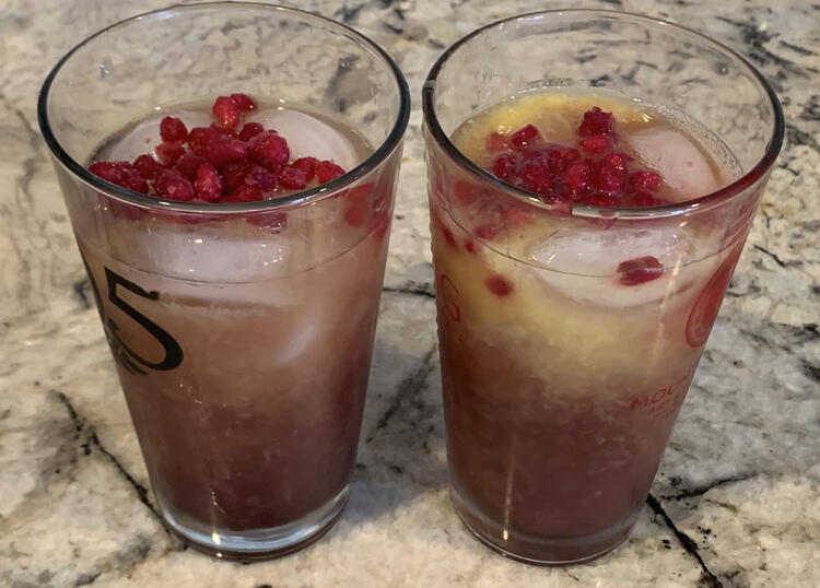 Image shows two clear glass cups side by side with ice and red-ish liquid and pomegranate seeds on top.