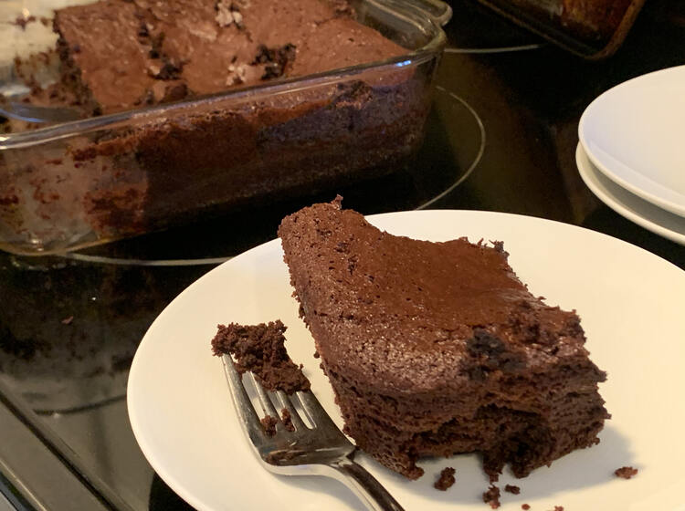 Image shows a corner piece of brownie on a white saucer with the glass casserole dish two thirds full behind it. Off to the side are two more saucers stacked.