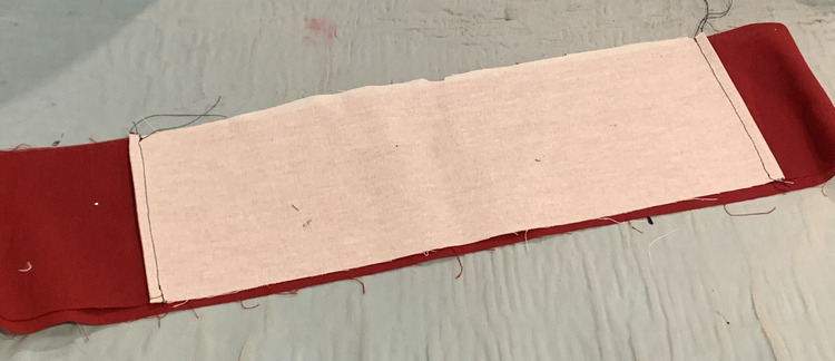 Image shows the waistband turned inside out showing the white interfacing on the inside front of the waistband. Either side shows a black threaded seam running up it.