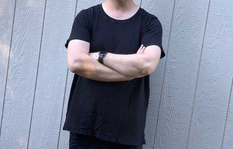 Image shows the torso of a white man wearing a black tee with his arms crossed in front of him. He stands in front of a white wall making his shirt pop a bit. Image is taken from his neck to right below the tee.