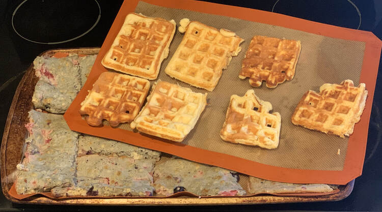 Image shows A cookie sheets with a Silpat filled with blue tinged pancakes. On top, at an angle, sits another Silpat with seven waffles lined up on it.