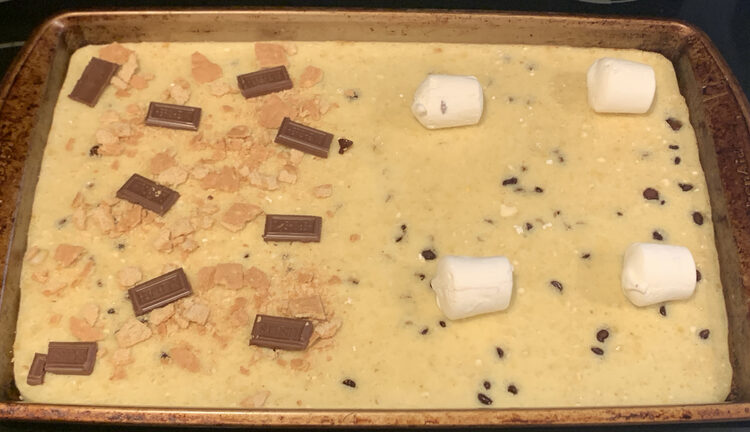 Image shows a sheet pan of baked pancake with the odd chocolate chip showing through from the bottom. The left side has rectangles of chocolate on it surrounded by graham crumbs. The right side has four evenly spaced large marshmallows with a hint of brown on one.