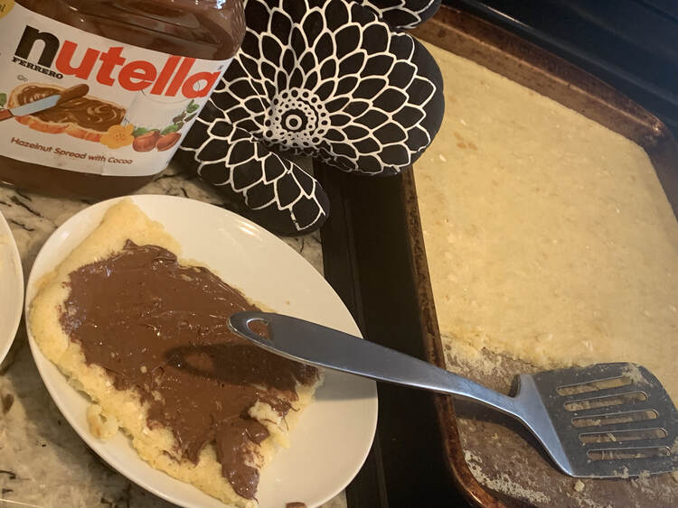 Image shows a cookie sheet with a strip of pancakes missing and a metal flipper on the right. On the left is a jar of Nutella, an oven mitt, and a play with a Nutella decorated square pancake on it.