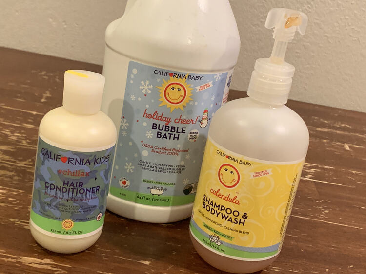 Image shows a half gallon jug of holiday cheer! bubble bath with a pump bottle of calendula shampoo and bodywash to the right and a small hair conditioner to the left.