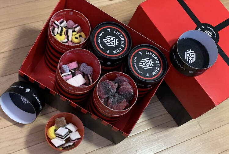 Image shows a closed gift box of licorice to the right and an opened box to the left. At the bottom left there's a red plastic cup with licorice in it next to several opened canisters.