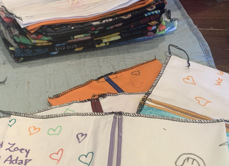 Image shows a staggered stack of inside out pouches showing one of their zipper ends. In the background is a stack of flat cinch pouches that I was working on at the same time.